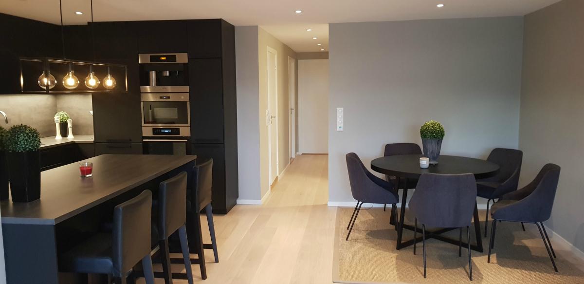 Kjøkkenet i åpen løsning og rundt spisebord