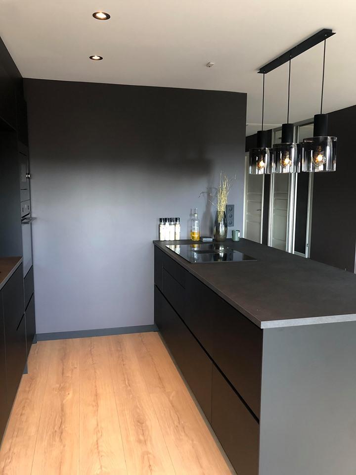 Halvøy med benkeventilator på det koksgrå, sorte kjøkkenet